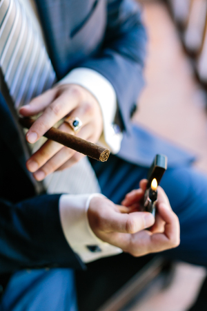 cheroot: wedding, elegance, high fashion concept. tough arms of man, dressed in dark blue costume for celebration with snowy white cuffs, lightening big expensive cheroot Stock Photo