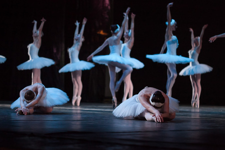 dancing, tradition, advancement concept. on the stage of the theater group of female ballet dancers in white tutus and leotards, two of them fell down and others dancing on the tips of their toes Stock Photo