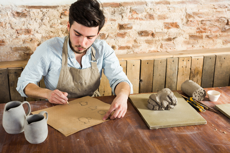 ceramicist: potter workshop, artisan tools, ceramics art concept - young man works with design of future utensil products, a ceramist sitting behind desk near tools, fireclay and finished pitchers Stock Photo
