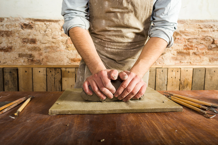 fireclay: potter, workshop, ceramics art concept - closeup on male hands modeling raw clay, a ceramist work with material on wooden table with fireclay and sculpting tool set, front view