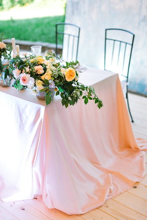 dining, flora, spring concept. on the coner of the table all covered by huge light pink cloths there is great bouquet made of different types of rose in shades of orange and pink colours