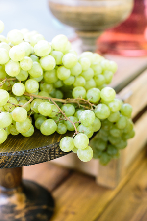 food, dining culture, freshment concept. in the wooden vase of rich dark color there are green juicy bunches of grape place on the dining table like decoration and refreshments Stock Photo