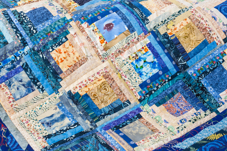 patchwork, handmade, sewing, interior, home cosiness concept - colourful folksy quilt in blue shades made of ornate snippets with floral prints stitched together in form of squares Stock Photo