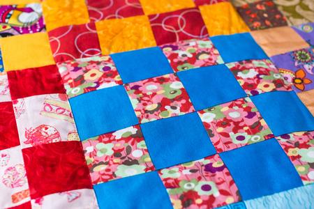 hecho en casa, interior, diseño, artesanía, imaginación, concepto de prenda: campo textil multicolor cosido de cuadrados de algodón brillante con puntadas invisibles según el principio del mosaico
