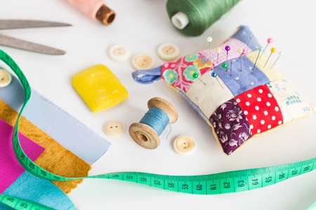 closeup sewing tools , patchwork, tailoring and fashion concept - working environment on a white table, thread spools, buttons, meter, pincushion, scissors, pieces of colored patchwork fabric, soap Фото со стока