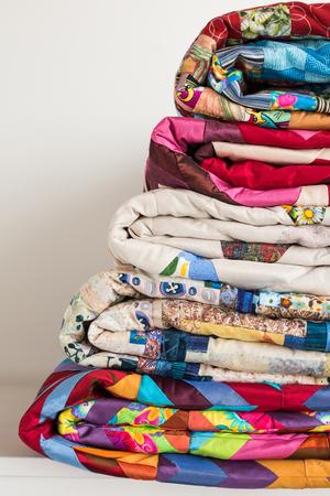naaien en mode concept - close-up stapel kleurrijke dekbedden, mooie beddenspreien gestapeld in verschillende rijen in de hoogte voor opslag, te koop patchwork producties op witte achtergrond, kopie ruimte, verticaal