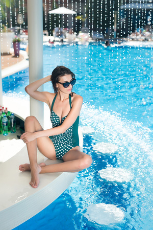 rest, fashion, appearance concept. smoking hot woman wearing green swimsuit with polka dots in vintage style and sunglasses sitting on the edge of swimming pool with clear sky blue water
