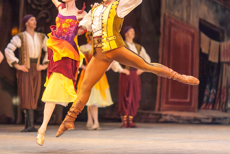 synchronously: amusement, grace, dancing concept. ballet duet of male and female dancers dressed in bright multi colored costumes in yellow shades floating above the stage holding each other Stock Photo