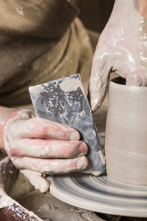 pottery, workshop, ceramics art concept - closeup on male fingers sculpt new utensil with a tools and water, mans hands working with potters wheel and raw fire clay, close view, vertical