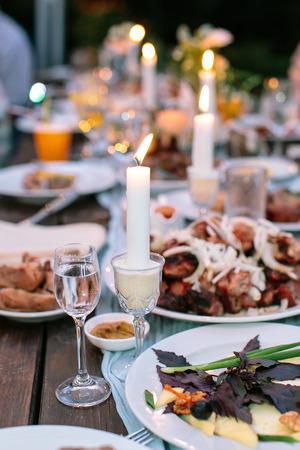 carnes y verduras: la comodidad, la comida, el concepto de celebración. en la mesa de jardín de madera sin telas hay platos con deliciosos platos, carnes y verduras, vasos con bebidas y velas