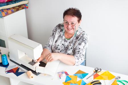 de lachende vrouw met bril op de naaimachine in atelier. het proces van het maken van lappendeken. de vrouwelijke modeontwerper in een workshop. concept van kleine bedrijven. handwerk.