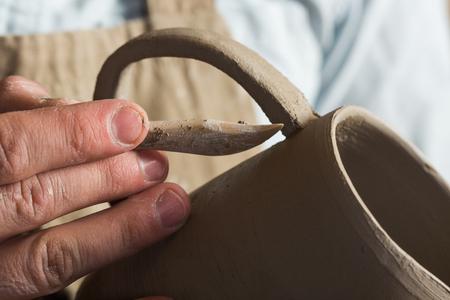 trabajo manual: potter, workshop, ceramics art concept - manos de ceramista trabajando con productos de arcilla sin hornear, dedos de craftsmans sosteniendo la jarra de arcilla y herramienta de corte Foto de archivo