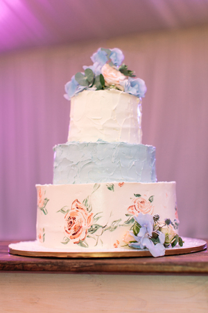 topper: party, treatment, sweet life concept. on the flat dish there is marvelous three-tiered birthday cake made of white and blue cream and decorated with various flowers