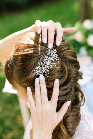 style, femininity, decoration concepr. in soft curly light brown hair of young woman there is shining barrette with diamonds in form of leaves and flowers