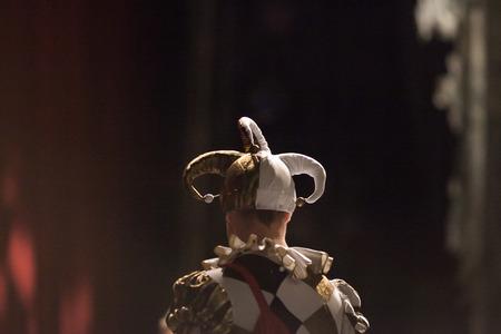 outfit, theater, opwinding concept. achterkant van de jonge man gekleed in kostuum van de hofnar met grappige dwazen pet en lichte jas met zwarte en gouden rhombuses