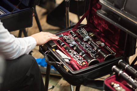 tenderly: music, performance, equipment concept. arm of player touching tenderly disassembled matt black clarinet, kept in small special case with gorgeous velvet lining of beautiful burgundy color