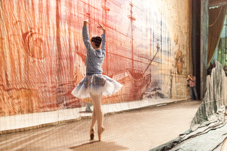 decoration, backstage, theater. man with camera taking photos of magnificent ballerina wearing for rehearsal in tutu and blue tracksuit top trying few movements Stock Photo