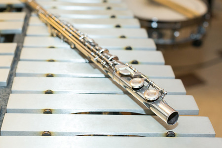 flute key: symphonic and brass band, percussion and wind instrument concept - beautiful closeup on western concert flute lies on beige bars of xylophone, orchestra, ensembles, jazz concerts, selective focus Stock Photo