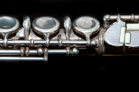flute key: wind instrument and symphonic music concept - closeup on western concert flute body with keys on black background surface, middle section of oldest and most widely used brass tool, macro