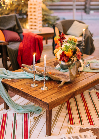 comfort, decoration, rest concept. magical atmosphere created with cosy armchairs, carpets, low wooden table with bouquet of flowers on it and of course burning candles in elegant silver holders Stock Photo