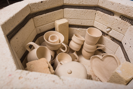 cerâmica, oficina, conceito de arte cerâmica - vista superior do forno elétrico para posterior torrefação de produtos de barro inacabada, forno para copos e jarros unbaked, fechar Foto de archivo