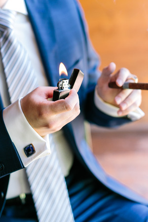 cheroot: success, smoking, celebration concept. well groomed arms of caucasian man, dressed in blue fashion costume made to measure with marvelous cufflinks, taking lightner and cheroot