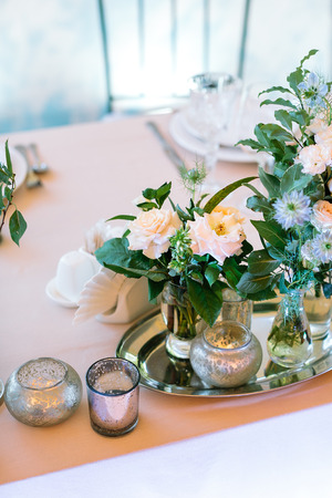 design, lifestyle, romance concept. on the peachy tableware there are lots of different small bunches made of roses and other flowers placed on the silver tray nearby with original candleholders
