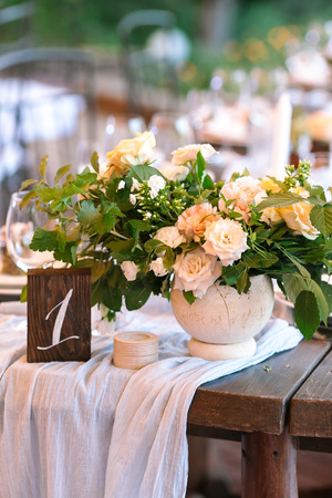 flora, wedding concept. delicate yellow and creamy roses mixed in bouquet for wedding decoration and placed among such verdure as leaves of oak, rosebush and raspberry in the vase of table number one