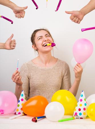 パーティー、お祝い、誕生日のコンセプト。extremelly 幸せな若い女の子の彼女たちが笑い、片方の腕で小さなピンクのバルーンを保持している他の青いキャンドル、誕生日を自分の歯笛します。