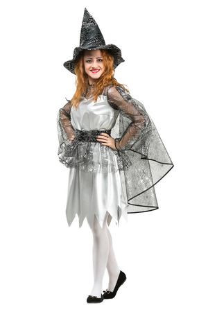 clothes, carnival, all saints day concept. fancy young woman with red hair dressed up like witch with her black pointed hat and mantle, almost all details of her costume are decorated with silver web