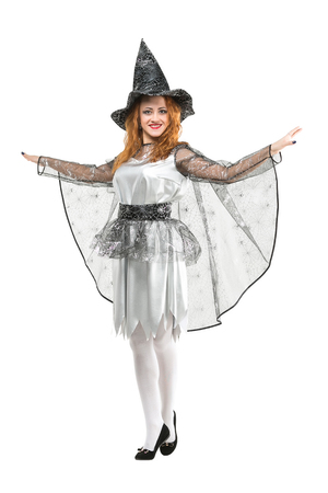 halloween, masquerade, entertainment concept. on white background isolated figure of excited red haired witch in wonderful carnival dress with pattern of web, it seems she is flying Stock Photo