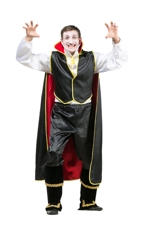 halloween, fairy tales, party concept. isolated figure of cute smiling guy with rised hands, he is wearing traditional costume of count dracula, that consists of black silk pants and jecket and mantle