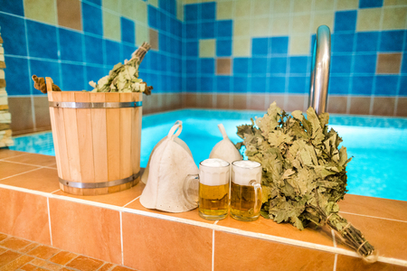 Bath accessories in the Russian bath. Bathroom items of traditional Russian sauna. two mugs of light beer, bathing caps, bath brooms against the pool. Recreation, spa, relaxation, rest concept.