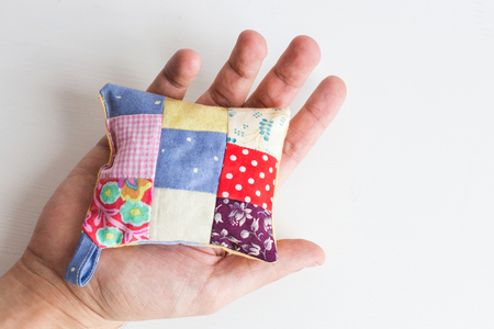 patchwork, quilting, sewing, tailoring and fashion concept - close-up on beautiful colorful stitched pincushion in human hand, macro on pillow with white background, flat lay, top view Stock Photo