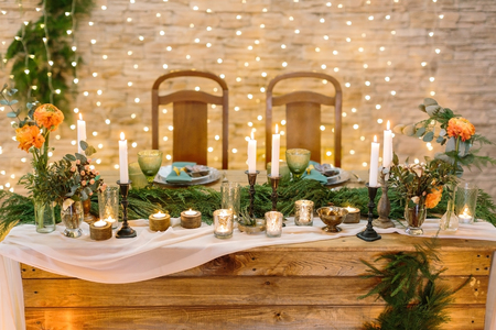 romantic table setting for two lovers with numerous of the candles in various candle holders, it also decorated with little bunches and lights on the background
