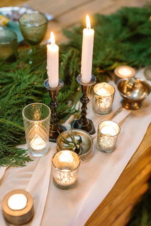 holiday decor of table consists of amount of candles in varied holders of glass and metal, in the center of table there are lots of green conifers branches