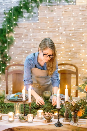 caucasian girl with wavy fair hair making floral design of table, decorating it with conifers branches, she is wearing glasses and simple but adorable denim shirt