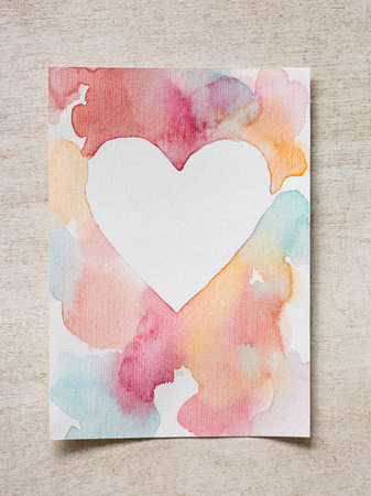 on the wooden desk there is greeting card that id made by artist with watercolors and construction paper that has rough surface Stok Fotoğraf