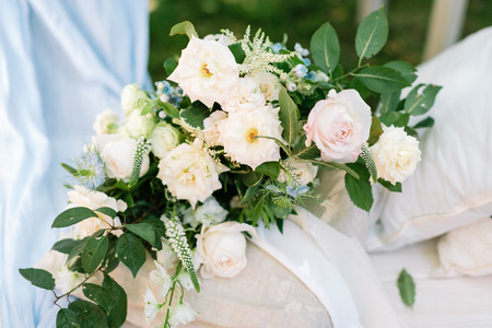 marvelous bouquet composed of various flowers, few kinds of roses, and brunches of rosebush, it placed on the pillow in linen pillowcase