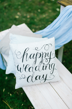 on the garden bench there is snowy white pillow with engagement congratulation printed in italic type of vintage style with different curls Stock Photo