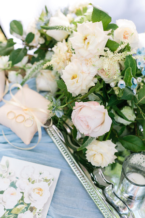 wonderful bridal bouquet of elegant creamy and pink roses decorated with small blue flowers placed on the silver shining tray nearby with pillows for rings