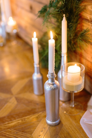 handmade, home atmosphere, cosiness concept. original work of an artist, bottles of different sizes and forms covered by silver paint and used like a candleholders, they are shining in light of fire