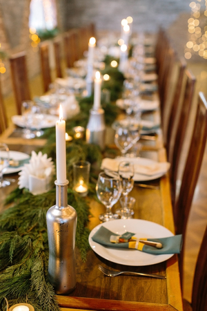 wedding decor, interior, illumination concept. close up of served holiday table with candles in original holders that looks like bottles, among them there are fresh branches of conifer trees Archivio Fotografico