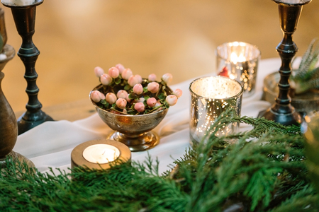 decor, interior, cosiness concept. romantic tableware decorated with lots of conifers branches, candles in holders of different forms, sizes and style and bowl with posy of peachy berries