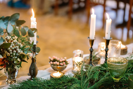 bright fires of feast candles that decorate the table, they are lightening posies of various leaves and bright conifer branches in fresh green colour