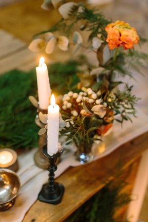 decoration, interior, romance concept. nearby with small but charming posies composed of small flowers, rose and various leaves there are few tall candles in different holders of wood and metal