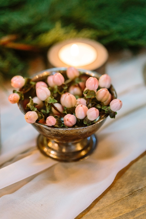 treatment, floristic service, tableware comcept. on the wooden table covered with white drapping there is small copper bawl with little posy with pink berries that look like tiny peaches