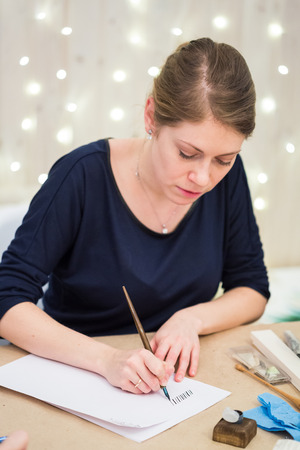 calligraphy, painting, creativity concept. adorable woman artist with fair haires and delicate arms wearing dark blue shirt and golden ring, she is drawing sticks with thin quill Stock Photo