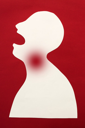 concept of human disease diagnosis and pain localization on silhouette - contour of abstract white man with opened mouth and severe pain in the throat, isolated on red background, top view, flat lay