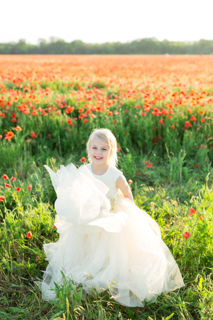 girl model, poppies, wedding, fashion, children, nature and summer concept - beautiful laughing baby girl bridesmaid with white hair playing in a field of poppies with her white wedding dress